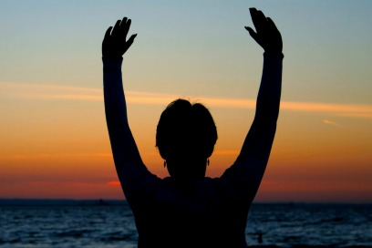 woman facing a sunset with her hands up over her head