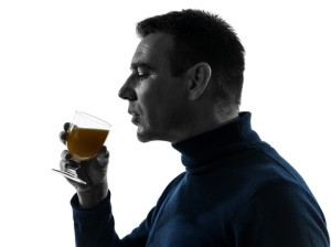 side shot of man drinking a beverage out of a glass for stress relief